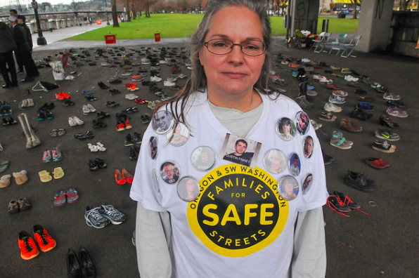 """Kristi Finney, whose son Dustin was killed when he was hit from behind by a truck while biking in 2011, stands before 421 pears of shoes, which symbolize those killed by traffic in Oregon so far this year. The average person is indifferent to this until it happens to them,"""" she told Bike Portland."""